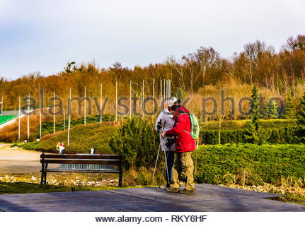 Poznan, Poland - February 10, 2019: Elderly couple standing with hiking sticks next to a wooden bench having a break at the Malta park on a cloudy day - Stock Photo