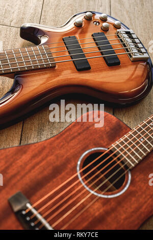 Choosing a guitar...Top view on two perfect polished musical instruments: acoustic and electric guitars are lying on the wooden floor in a music shop. Musical instruments. Music concept. Guitar body - Stock Photo