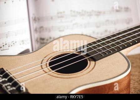 Ukulele chords. Close-up photo of ukulele guitar and music notes against of wooden background. - Stock Photo