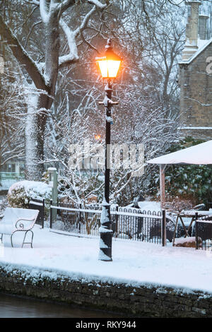 Street lamp in Bourton on the Water in the early morning snow. Bourton on the Water, Cotswolds, Gloucestershire, England - Stock Photo