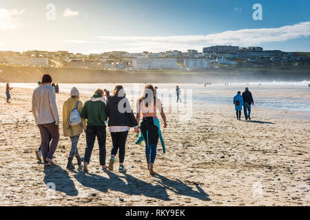 A group of friends walking down to the sea at Fistral Beach in Newquay in Cornwall. - Stock Photo