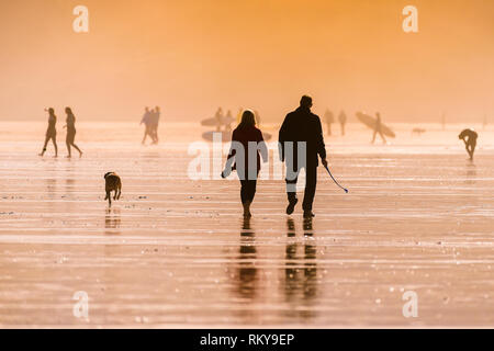 People walking their dog on Fistral Beach in late evening sunlight. - Stock Photo