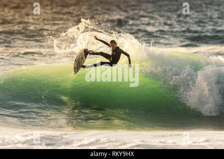 A young surfer riding a wave at Fistral in Newquay in Cornwall. - Stock Photo