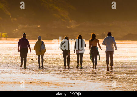 A group of people walking across Fistral Beach in evening light. - Stock Photo