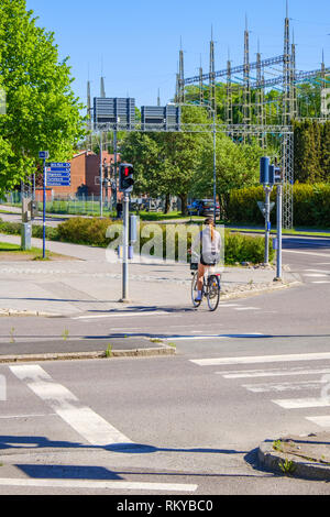 Young woman cycling at a pedestrian crossing on a city street - Stock Photo