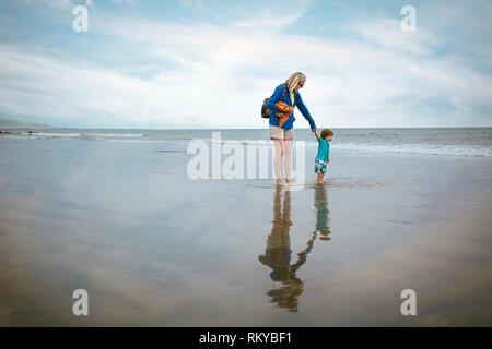 Young child and mother holding hands at the waters edge on Coronado Beach in California. - Stock Photo