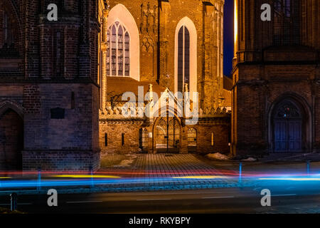 Church of St. Francis and St. Bernard (Bernardine Church) with entrance gate and bell tower, on the left - St. Anne's Church. At winter night, in Viln - Stock Photo