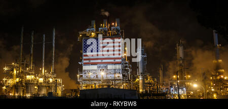 Panorama of large American flag displayed on the side of an oil refinery at night. - Stock Photo