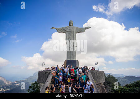 Clear view of a crowd of tourists on top of the Corcovado mountain in Rio de Janeiro with the Christ statue towering over them and landscape behind - Stock Photo