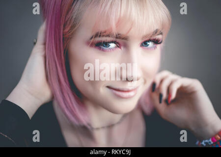 Portrait of teen girl with pink hair and pierced nose looking at camera. - Stock Photo