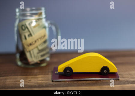 Saving money for vacation theme with yellow wooden car and money in jar - Stock Photo