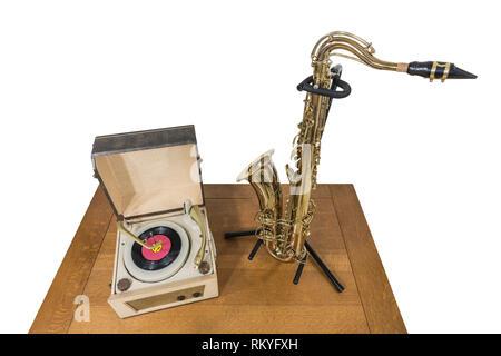 Vintage record player and saxophone on wood table isolated on white. - Stock Photo