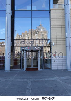 Malmaison hotel reflected in Sleeperz hotel entrance Dundee Scotland  January 2019 - Stock Photo