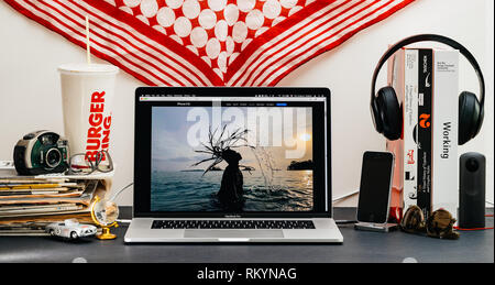 LONDON, UK - SEP 13, 2018: Creative room table with Safari Browser on MacBook Pro laptop showcasing Apple Computers website latest iPhone Xs smartphone with photo sample by dual camera - Stock Photo