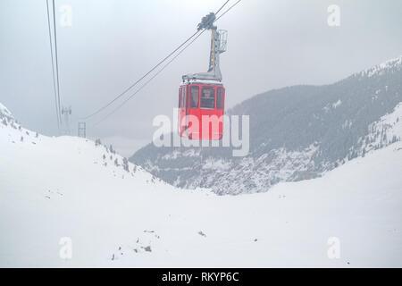 red cable car on snow storm in Fagaras Mountains, Balea lake, Sibiu county,  Transylvania, Romania, Europe - Stock Photo