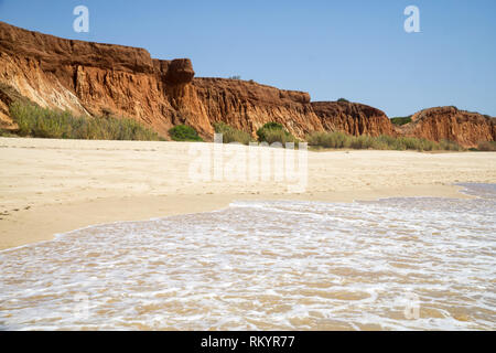 High cliffs along Falesia Beach and The Atlantic Ocean in Albufeira, Algarve, Portugal. Sunny summer day, blue sky. - Stock Photo