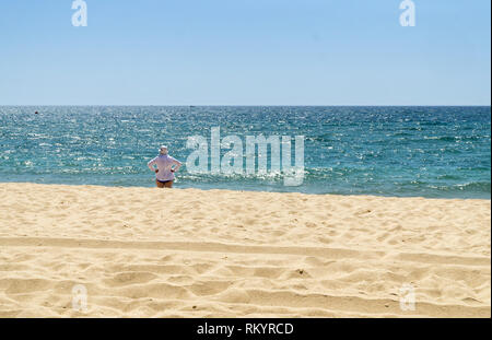 Mature woman in white shirt and white hat is standing on the beach and watching the sea in sunny summer day. - Stock Photo