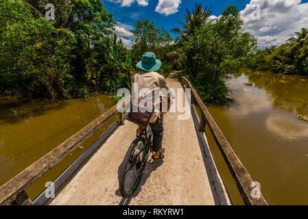 A man bicycling along the backwaters, Cai Lay, Mekong Delta, Vietnam. - Stock Photo