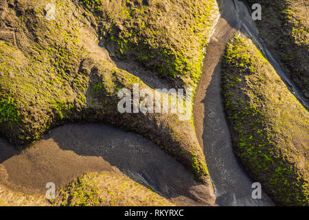 Sea tide on the moss-covered rocky beach, Bali, Indonesia - Stock Photo