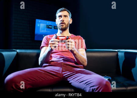 Man playing video games with gaming console and joy stick sitting on the couch in the dark room of the playing club - Stock Photo