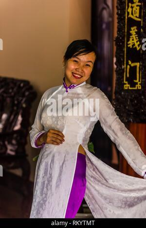 A Vietnamese woman wearing the traditional women's costume Ao Dai, Hoi An, Vietnam. - Stock Photo