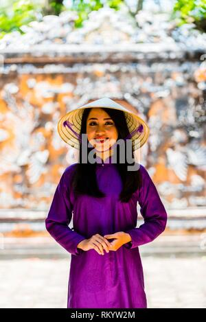 Vietnamese woman wearing the traditional ao dai costume in the Imperial City, a walled palace within the citadel of the city of Hu? which is the - Stock Photo