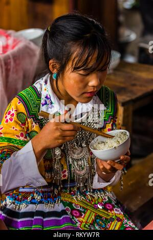 Flower Hmong (hill tribe) women eating at the Sunday market at Bac Ha, northern Vietnam. Every Sunday ethnic minorities come from surrounding - Stock Photo