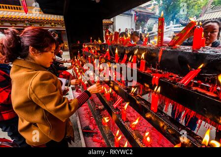 Red Candles are an age old traditional part of Buddhist rituals. They are placed in front of Buddhist shrines or statues and images of the Buddha as - Stock Photo
