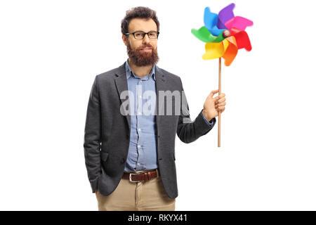 Bearded man holding a spinning pinwheel isolated on white background - Stock Photo