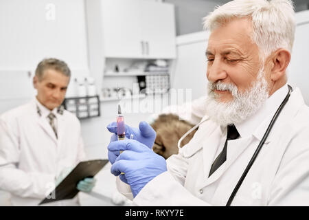 Cheerful elderly veterinarian holding needle for injection. Doctor with gray hair and beard wearing in white medical uniform and blue gloves. Assistant standing near patient, holding folder. - Stock Photo