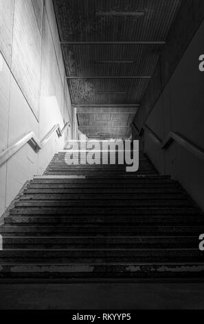 Staircase from an underground passage with concrete walls and metal railing in a low light - Stock Photo