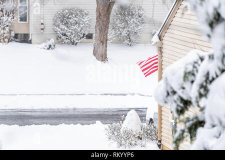 Residential neighborhood in United States with American Flag waving in wind during winter storm and snow - Stock Photo