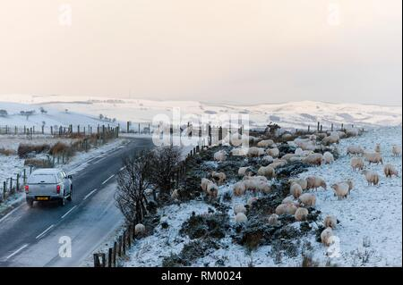 A car drives along the B4520 (Brecon Road) through a wintry landscape on the Mynydd Epynt moorland, near Builth Wells in Powys, Wales, UK. - Stock Photo