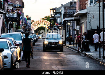 New Orleans, USA - April 22, 2018: Old town in Louisiana famous town at evening dark night with car on road Dumaine street and illuminated Armstrong P - Stock Photo