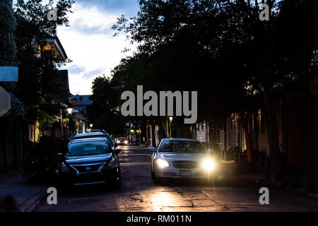 New Orleans, USA - April 22, 2018: Old town Bourbon street in Louisiana famous town city at night with car on road and headlights turn - Stock Photo