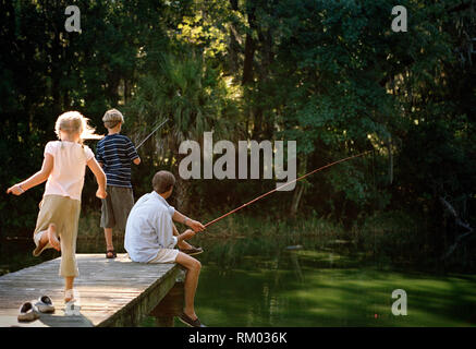 Young boy fishing off a jetty with his father as his sister joins them. - Stock Photo