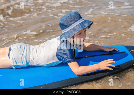 Happy baby boy - young surfer ride on surfboard with fun on sea waves. Active family lifestyle, kids outdoor water sport lessons and swimming activity