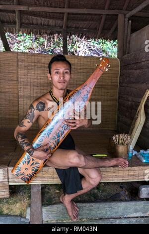 Penan man playing sape at Sarawak Cultural Village also named as Sarawak Living Museum, Damai, Malaysia - Stock Photo