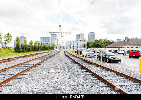 New Orleans, USA - April 23, 2018: Old town street in Louisiana famous city with railroad on Dumaine street and tracks with parked cars and cityscape - Stock Photo