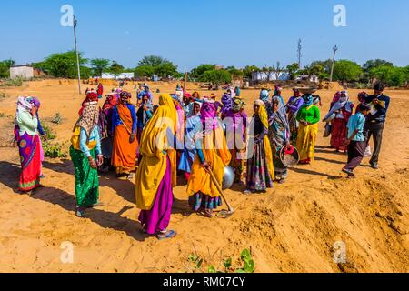 Rajasthani women in bright colors working (carrying dirt) at a construction project along the Jaipur-Agra Road, India. - Stock Photo