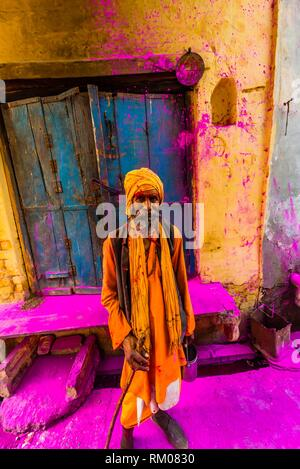 A saddhu (Holy man) walks down the street after a procession has passed throwing colored powders, Chhadi Mar Holi ( a local celebration during Holi, - Stock Photo