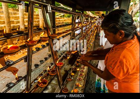 Buddhist Pilgrims lighting oil lamps outside the Sri Maha Bodhi. The sacred bodhi tree. Anuradhapura, North Central, Sri Lanka. - Stock Photo