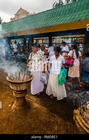 Buddhist Pilgrims lighting incense sticks outside the Sri Maha Bodhi. The sacred bodhi tree. Anuradhapura, North Central, Sri Lanka. - Stock Photo