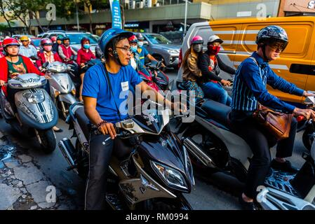 Uber drivers in Saigon drive motorcycles, Ho Chi Minh City (Saigon), Vietnam. There are over four million motorbikes in the city. - Stock Photo