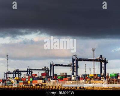 International Trade - containers being loaded and unloaded onto container ships at Felixstowe, the UK's main container port for imports and exports - Stock Photo