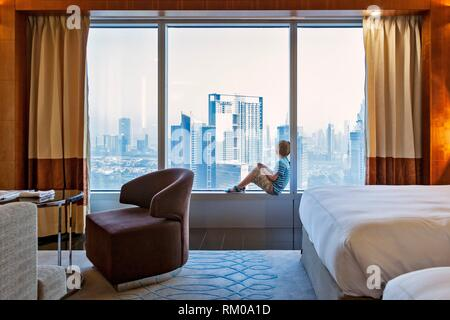 A 7 year old caucasian boy looks out at the Dubai skyline from the Jumeirah Emirate Towers Hotel room window, Dubai, Dubayy, United Arab Emirates. - Stock Photo