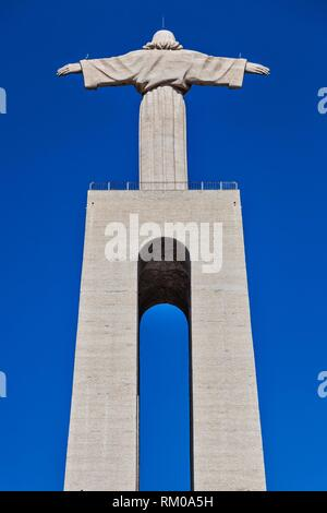 View from the rear and below of the Cristo Rei (Christ the King) monument located on the Almada Plateau, designed by the sculptor Francisco Franco de - Stock Photo