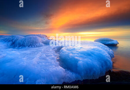 Beautiful  orange and golden colored sunrise clouds and blue sky over frozen lake horizon - Stock Photo