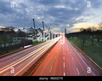 Light trails of cars driving/commuting past modern architecture in a city - Munich, Germany - Stock Photo