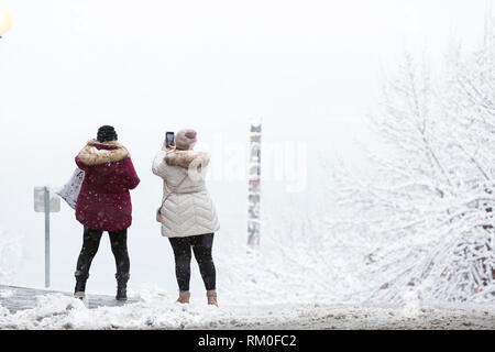 Seattle, Washington: Visitors stop to take a photo of Elliott Bay as a strong winter storm blankets Seattle in six inches of snow. In the distance is  - Stock Photo